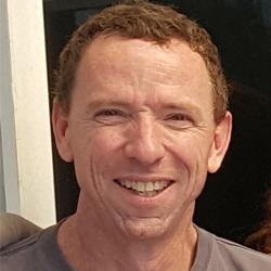 A masculine presenting person smiles at the camera. They have curly hair