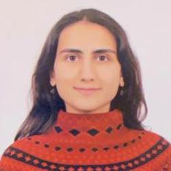 A feminine presenting person with black and a red knit jumper